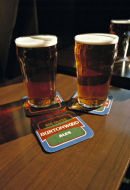 Two pints of bitter on pub table.