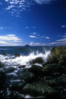 Waves splash over rock with Ailsa Craig in background