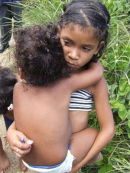 Young girl carrying her sister